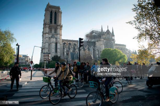 Cyclists pass by the NotreDame de Paris Cathedral in the aftermath of a fire that devastated the cathedral in Paris on April 17 2019 French President...