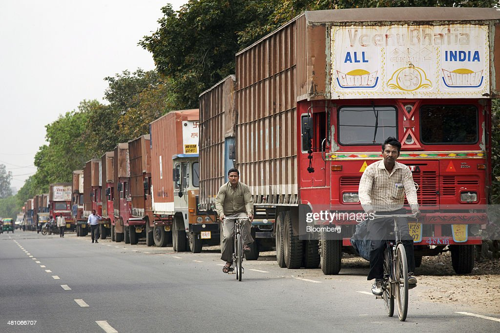 Cyclists pass parked trucks on the roadside in Gurgaon, India, on Wednesday, March 26, 2014. Indian stocks rose, sending the benchmark index to a record, after the rupee rose to an eight-month high and sovereign bonds gained on speculation the worlds largest democracy will elect a government capable of reviving economic growth. Photographer: Kuni Takahashi/Bloomberg via Getty Images