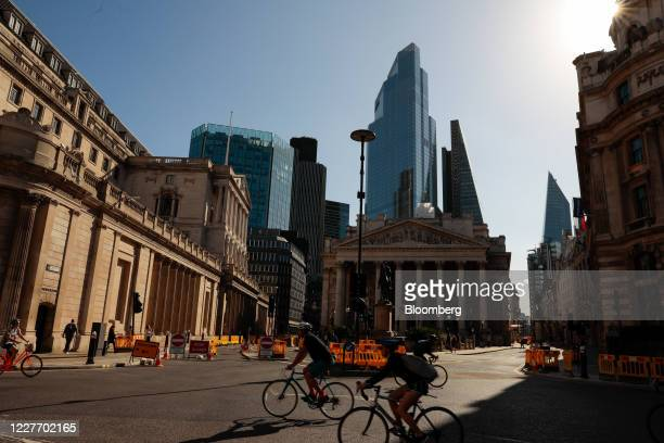 Cyclists pass through an interchange in view of the Bank of England left and the Royal Exchange in the City of London UK on Monday July 20 2020 UK...