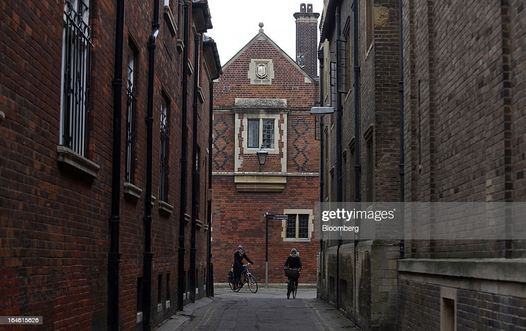 Cyclists pass University of Cambridge buildings in Cambridge, U.K., on Friday, March 22, 2013. In 2011, the U.K.'s government unveiled a plan to reduce state spending on higher education and shift more of the costs to students through tuition increases and a loan program. Photographer: Chris Ratcliffe/Bloomberg via Getty Images