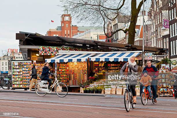 Cyclists passing Flower market stand
