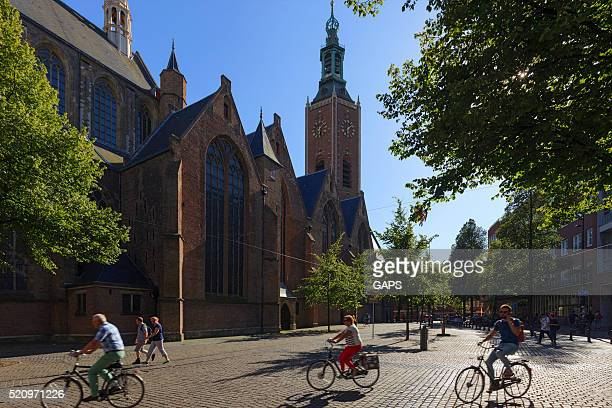 cyclists passing the hague's grote kerk - hague stock photos and pictures