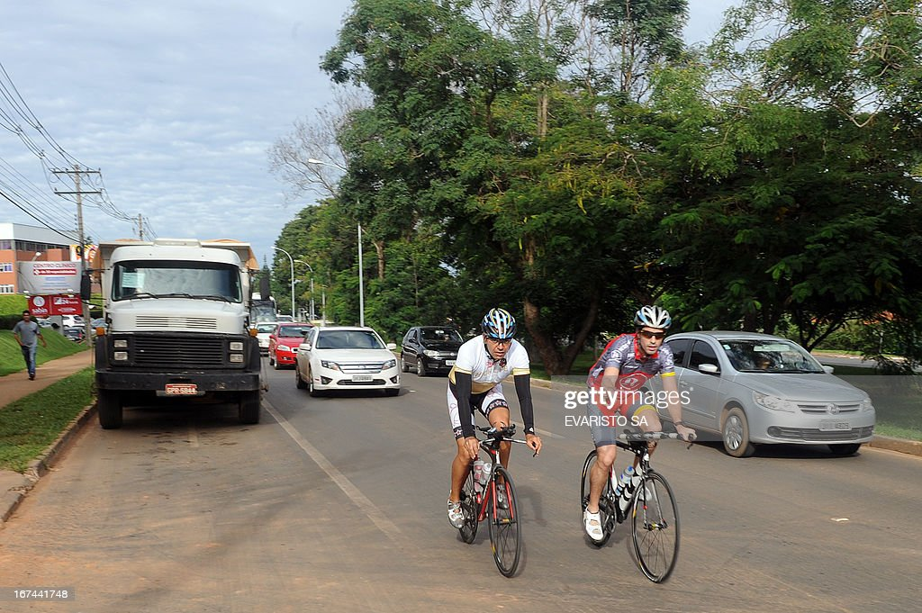 Cyclists pedal along a road without bikeways in South Lake in Brasilia, sharing the street with buses and cars, on April 16, 2013