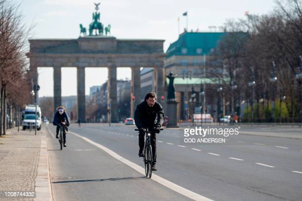 Cyclists pedal along an almost deserted 17th June street leading up to Brandenburger gate in Berlin on April 1, 2020 as Germany continues its battle...