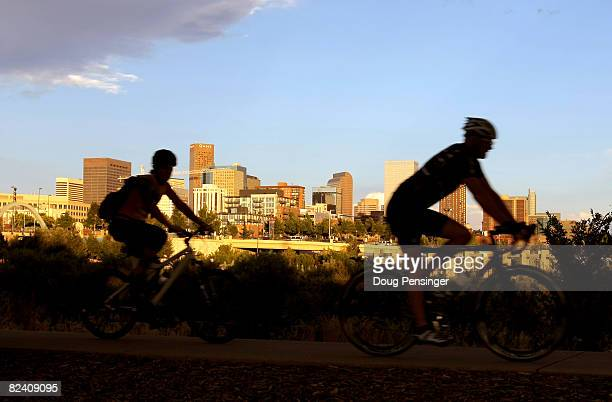 Cyclists pedal along the South Platte River across from the downtown city skyline on August 12 2008 in Denver Colorado The city is preparing to host...