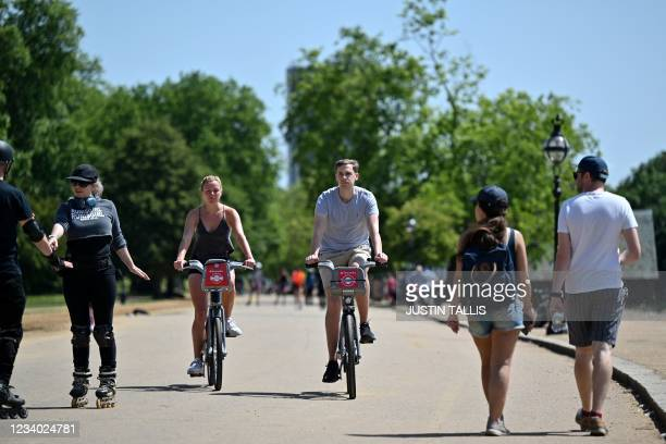 Cyclists pedal on a short-term hire bicycles in the sunshine in Hyde Park, central London on July 17 as forecasters expect the mercury to hit 31C in...