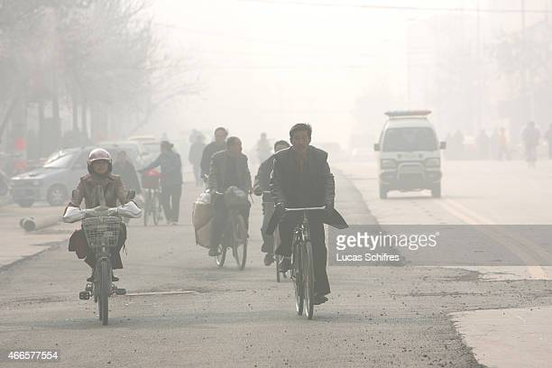 Cyclists pedal their way through mist and pollution on November 17 2007 in Taiyuan Shanxi province China China's rate of birth defects had risen from...