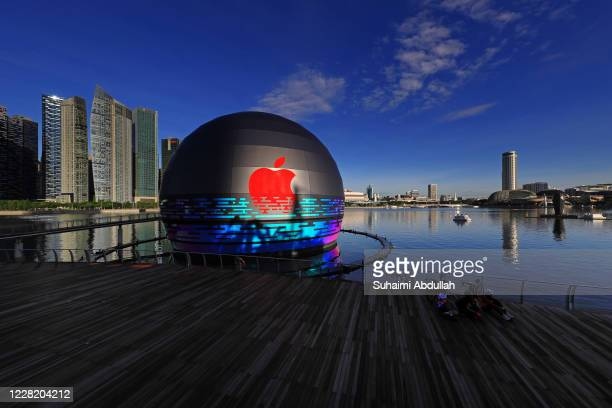 Cyclists pose for a photo in front of the new Apple flagship store at Marina Bay Sands waterfront on August 26, 2020 in Singapore. The store located...