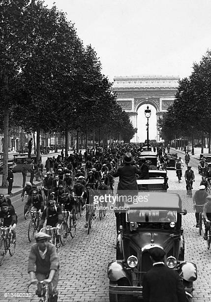 Cyclists probably competing in the Tour de France pass through the Arc de Triumph on the Champes Elysees