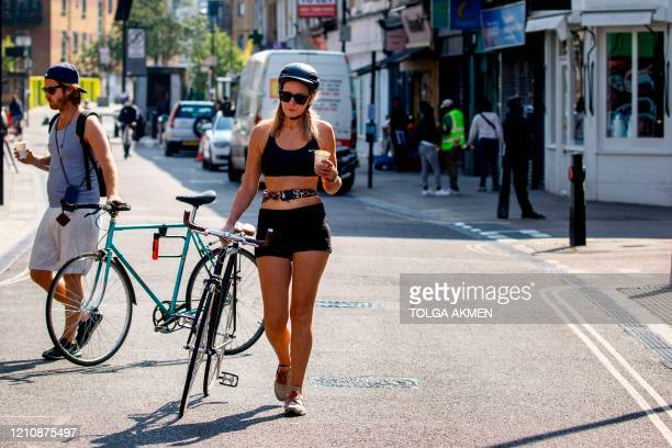 Cyclists push their bicycles as they walk on Broadway Market in east London on April 24, 2020. During the national lockdown due to the novel...