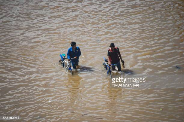TOPSHOT Cyclists push their bicycles through a flooded area after seasonal rains hit the area around Bandung West Java province on November 17 2017 /...