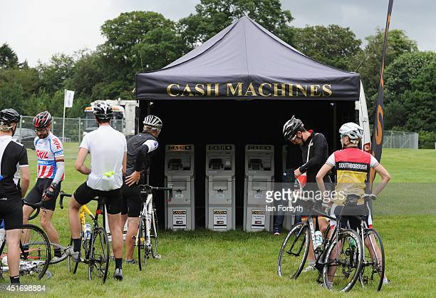 Cyclists queue for a cashpoint machine in the grounds of Harewood House in Yorkshire as visitors get ready for the start of the Yorkshire stages of...