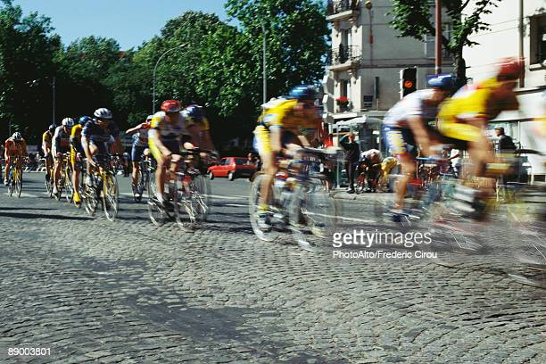cyclists racing on cobblestone street - cycling event stock pictures, royalty-free photos & images