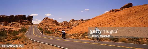 cyclists racing on road through red rock formations - timothy hearsum bildbanksfoton och bilder