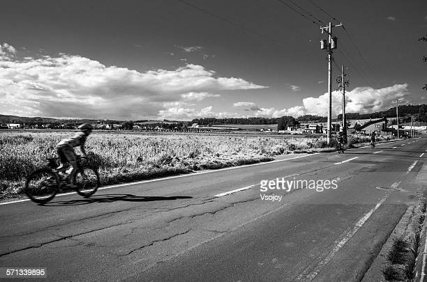cyclists racing on the road at kamifuranocho - vsojoy stock pictures, royalty-free photos & images