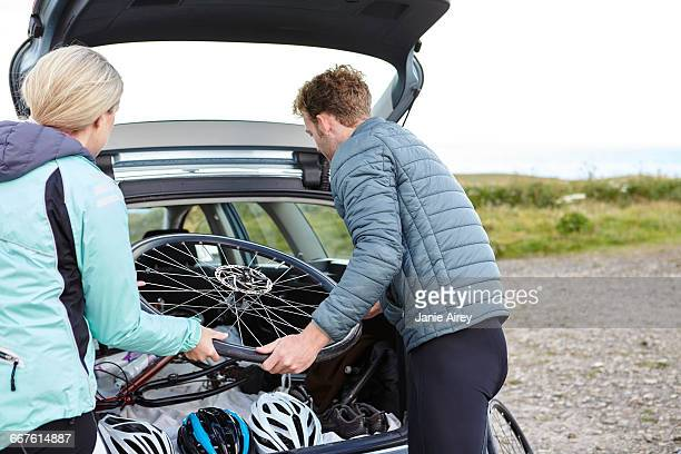 Cyclists removing bicycle from vehicle