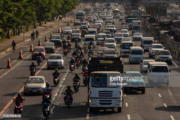 Cyclists ride along a bike lane alongside traffic on April 27, 2021 in Quezon city, Metro Manila, Philippines. Many Filipinos, including healthcare...