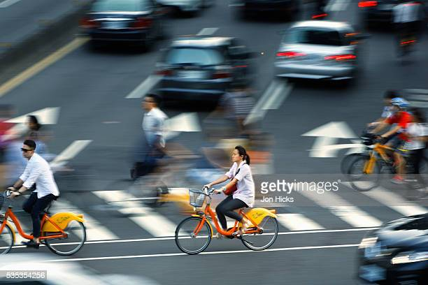 Cyclists ride along a city center crosswalk in Taipei, Taiwan