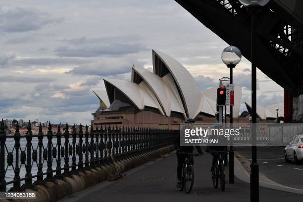 Cyclists ride along a quiet walkway under the Harbour Bridge in Sydney on July 19 amid a lockdown in Melbourne and Sydney as Australia seeks to...