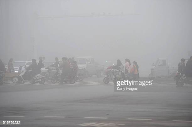 Cyclists ride along a road in heavy smog on April 8 2016 in Bozhou China Bozhou Meteorological Bureau issued a yellow alert to heavy fog on Friday...