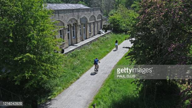 Cyclists ride along the Monsal Trail past the former Hassop railway station in the Peak District National Park in northern England on May 30, 2020...
