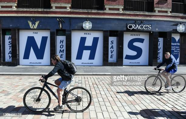 Cyclists ride bikes as they pass a giant logo of Britain's National Health Service , placed in the windows of a closed-down pub in appreciation of...