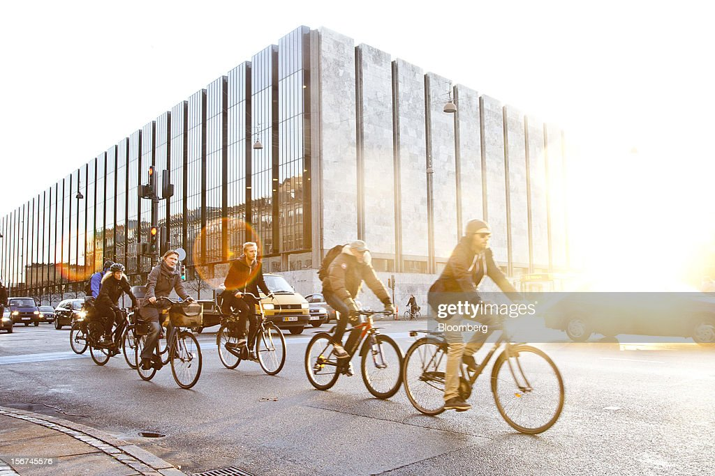 Cyclists ride bikes past the headquarters of Denmark's central bank in central Copenhagen, Denmark, on Monday, Nov. 19, 2012. Denmark's two-year yields sank to the lowest in almost three months in Copenhagen trading as Europe's debt crisis continues to drive investors north. Photographer: Linus Hook/Bloomberg via Getty Images