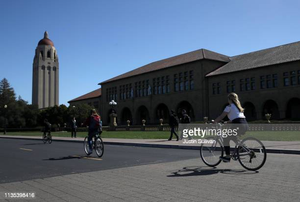 Cyclists ride by Hoover Tower on the Stanford University campus on March 12 2019 in Stanford California More than 40 people including actresses Lori...