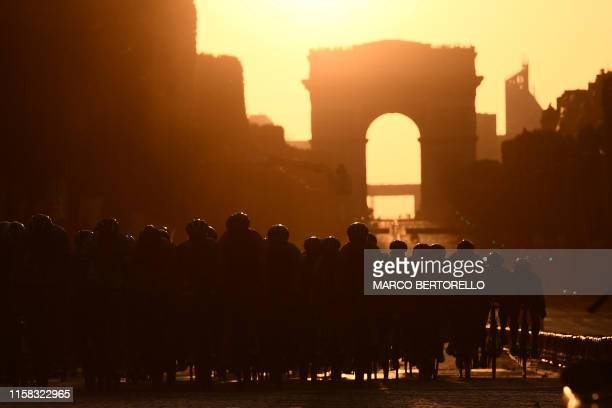 Cyclists ride dwon the Champs Elysees avenue with the Arc de Triomphe in background during the 21st and last stage of the 106th edition of the Tour...