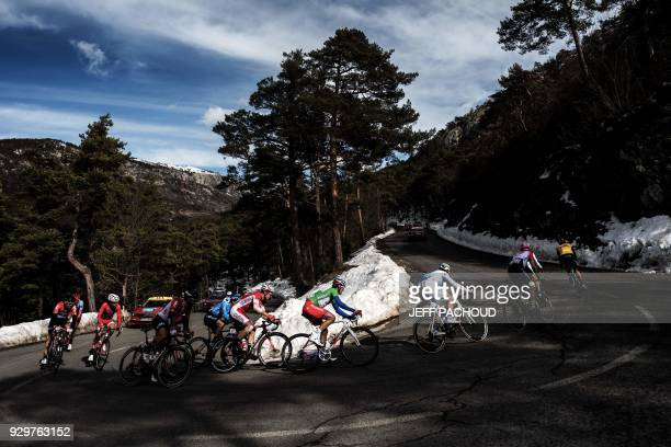 TOPSHOT Cyclists ride in a breakaway past snow during the sixth stage of the Paris Nice cycling race between Sisteron and Vence on March 9 2018 / AFP...