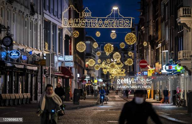 Cyclists ride in a scarcely dense street under Christmas decorations in the city centre of Amsterdam on November 12 during a partial lockdown in the...