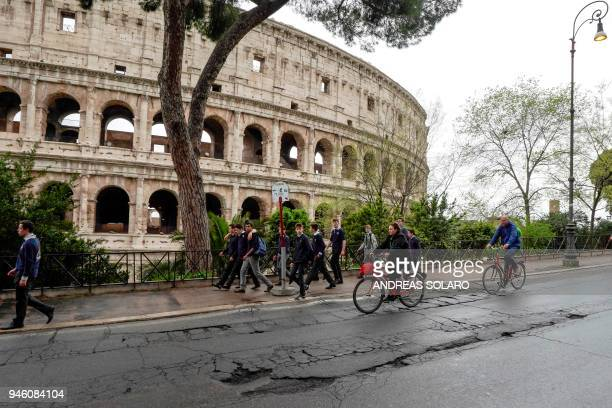 Cyclists ride over potholes on a road past the Colosseum in downtown Rome on April 12 2018 Romes roads problems have been existing for years due to...