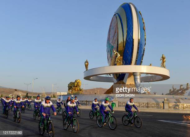 Cyclists ride past a 30-metre monument honouring cycling, which has become an important component of state propaganda that promotes a healthy...