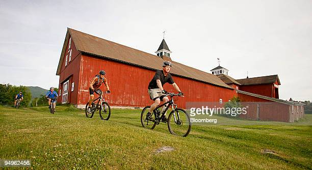 Cyclists ride past a barn on the Kingdom Trails in East Burke Vermont US on Wednesday June 17 2009 Kingdom Trails features 100 miles of mountain...