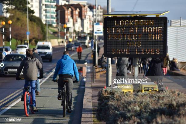 """Cyclists ride past a digital public safety notice saying """"Lockdown, Stay At Home, Protect The NHS, Save Lives"""" along the seafront at Westcliff on..."""