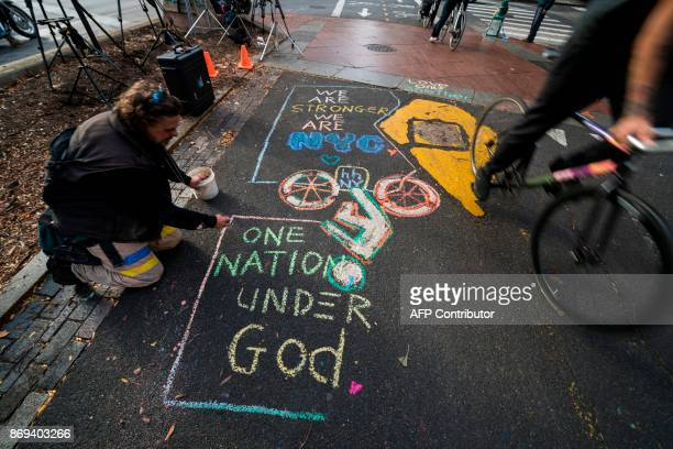 Cyclists ride past a message paying tribute to the October 31 terror attack victims in New York on November 2 2017 US President Donald Trump on...
