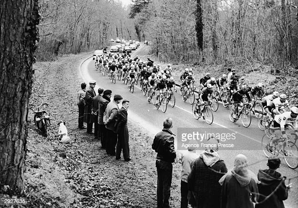 Cyclists ride past a small group of onlookers on a treelined road in the Forest of Fontainebleau shortly after the start of the Tour de France...