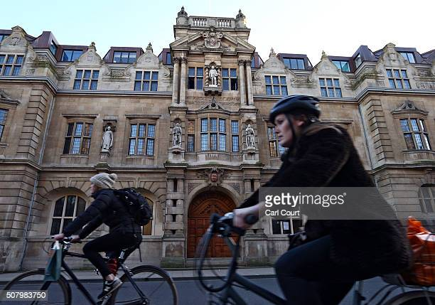 Cyclists ride past a statue of Cecil Rhodes displayed on the front of on Oriel College on February 2 2016 in Oxford England Oriel College has decided...