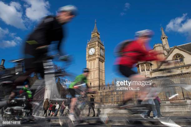 TOPSHOT Cyclists ride past the clock face of the Elizabeth Tower commonly referred to as Big Ben in Westminster central London on April 18 2017...