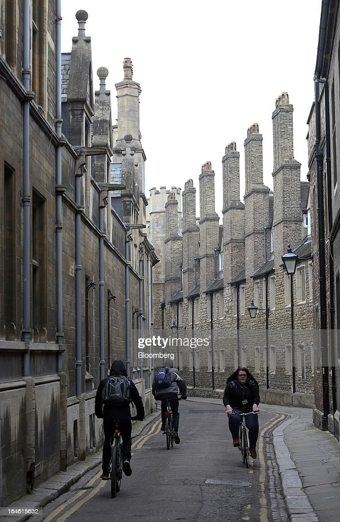 Cyclists ride their bicycles between University of Cambridge buildings in Cambridge, U.K., on Friday, March 22, 2013. In 2011, the U.K.'s government unveiled a plan to reduce state spending on higher education and shift more of the costs to students through tuition increases and a loan program. Photographer: Chris Ratcliffe/Bloomberg via Getty Images