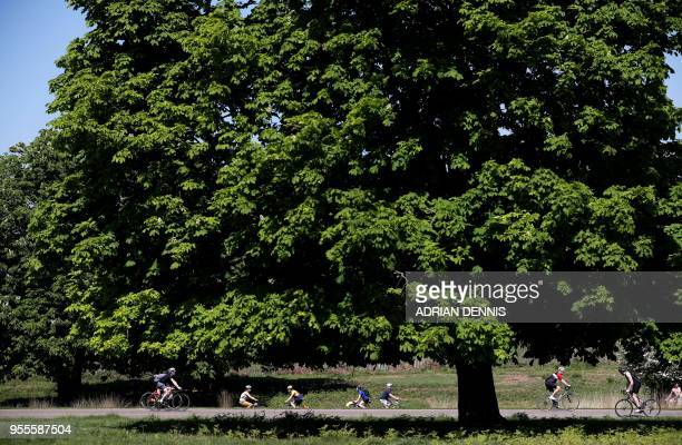 Cyclists ride their bicycles in the sunshine in Richmond Park in south west London on May 7 2018 Temperatures on Monday were predicted to reach 29C...