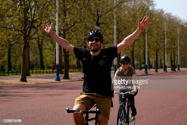 Cyclists ride their bicycles on The Mall road outside Buckingham Palace in central London on April 11 as life in Britain continues over the Easter...