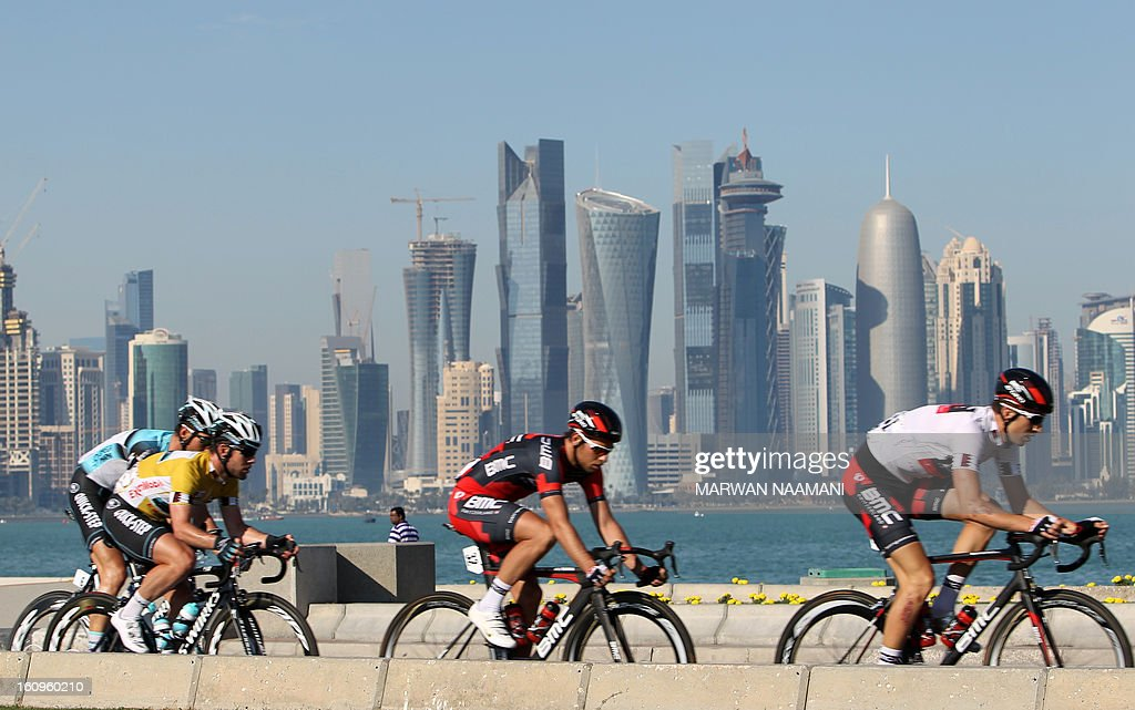 Cyclists ride their bikes in front of skyscrapers during the last stage of the 2013 Tour of Qatar, from Cyline beach to the Doha Cornich, on February 8, 2013