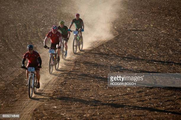 Cyclists ride through wheat fields during the prologue stage of the 2017 Cape Epic mountain bike stage race near Durbanville on March 19 in Grabouw...