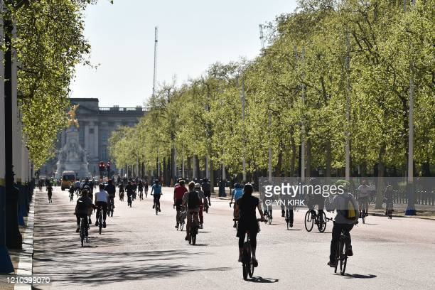 Cyclists ride up The Mall towards Buckingham Palace in central London on April 19 during the novel coronavirus COVID-19 pandemic. - The number of...