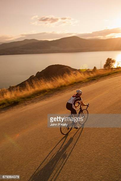 cyclists rides on scenic beach road at sunset - pantaloncini foto e immagini stock