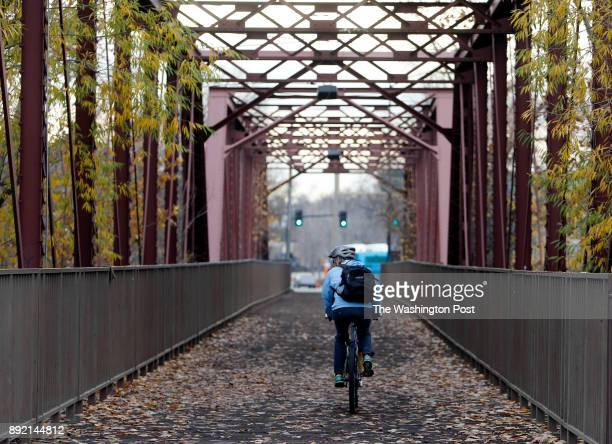 A cyclists rides over a former railroad bridge near Boise State University along the Boise River Greenbelt a 25mile nonmotorized trail that runs...