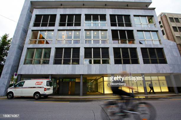 Cyclists rides past the building that houses the headquarters of Xstrata Plc in Zug, Switzerland, on Friday, Aug. 24, 2012. Glencore's planned...