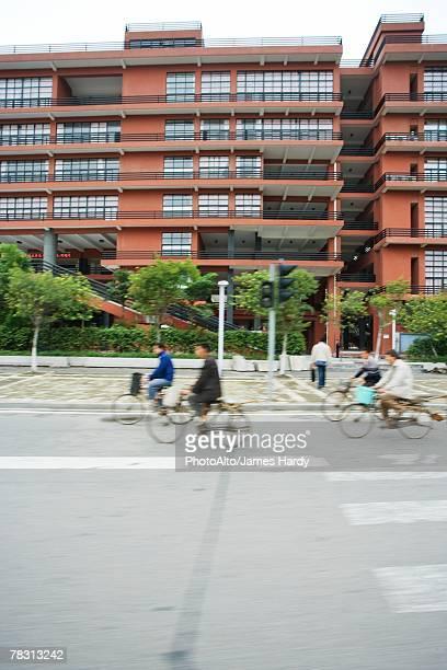 cyclists riding in street, blurred motion - passeren stockfoto's en -beelden