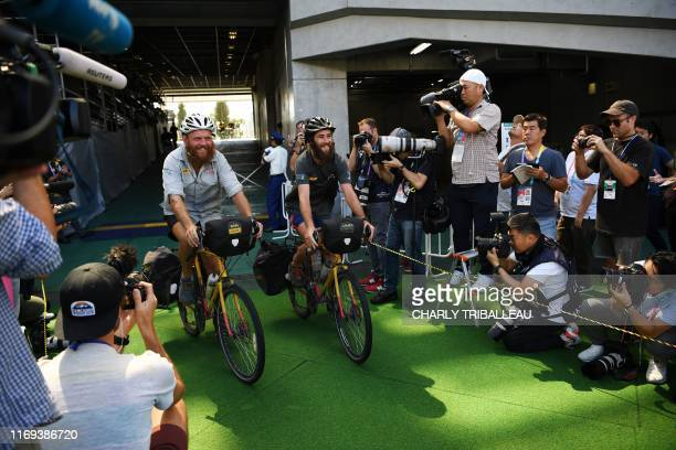 Cyclists Ron Rutland and James Owen arrive at the Tokyo stadium in Tokyo on September 19 as they complete their bike expedition from Twickenham ahead...